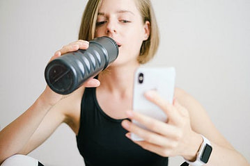 woman drinking water with cell phone